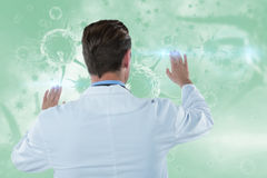 Composite image of rear view of doctor touching transparent interface 3d Stock Images