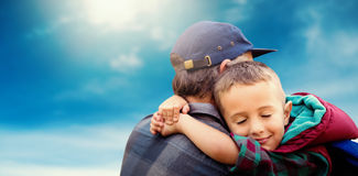Composite image of rear view of a father is embracing his son. Rear view of a father is embracing his son  against low angle of cloudy sky Stock Photos