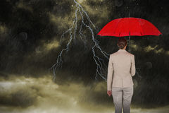 Composite image of rear view of female executive carrying red umbrella Stock Image