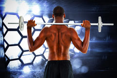Composite image of rear view of a fit shirtless man lifting barbell Royalty Free Stock Photo