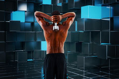 Composite image of rear view of a fit shirtless man lifting dumbbell Royalty Free Stock Photo