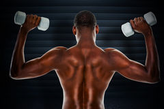 Composite image of rear view of a fit shirtless man lifting dumbbells Royalty Free Stock Images