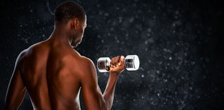 Composite image of rear view of a fit shirtless young man lifting dumbbell Stock Photography