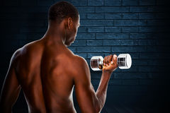 Composite image of rear view of a fit shirtless young man lifting dumbbell Royalty Free Stock Image