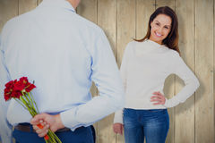 Composite image of rear view of man hiding roses behind back from woman. Rear view of man hiding roses behind back from woman against wooden planks Stock Photo
