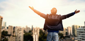 Composite image of rear view of a man raising his arms up. Rear view of a men raising his arms up against city against blue sky Royalty Free Stock Image
