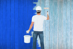 Composite image of rear view of man using paint roller Stock Photo