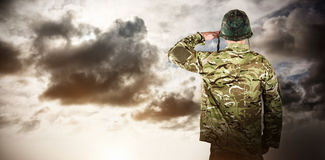 Composite image of rear view of military soldier saluting stock photo