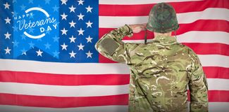 Composite image of rear view of military soldier saluting. Rear view of military soldier saluting against rippled us flag Royalty Free Stock Image