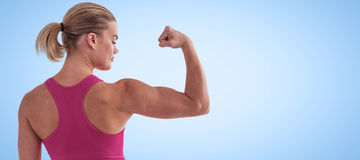 Composite image of rear view of muscular woman flexing muscles. Rear view of muscular woman flexing muscles  against blue background Royalty Free Stock Image