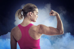 Composite image of rear view of muscular woman flexing muscles. Rear view of muscular woman flexing muscles  against cloudy sky Stock Images