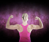 Composite image of rear view of muscular woman flexing muscles. Rear view of muscular woman flexing muscles  against dark background Royalty Free Stock Photo