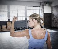 Composite image of rear view of muscular woman flexing muscles. Rear view of muscular woman flexing muscles  against gym Stock Images