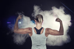 Composite image of rear view of muscular woman flexing muscles. Rear view of muscular woman flexing muscles  against smoke Royalty Free Stock Photo