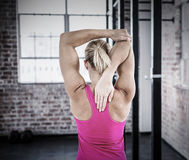 Composite image of rear view of muscular woman stretching her arm Stock Photos