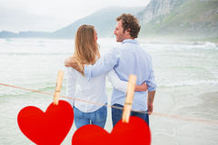 Composite image of rear view of a romantic couple at beach Royalty Free Stock Image
