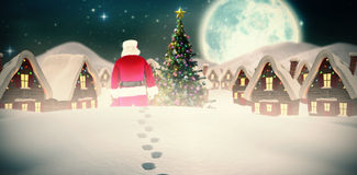 Composite image of rear view of santa claus holding a sack Stock Photo