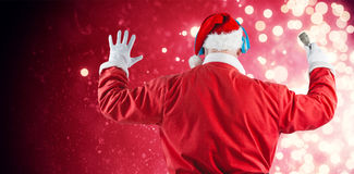 Composite image of rear view of santa claus listening to music. Rear view of Santa Claus listening to music against light design shimmering on red Royalty Free Stock Image