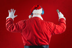 Composite image of rear view of santa claus listening to music. Rear view of Santa Claus listening to music against red snowflake background Stock Photo