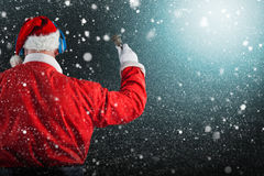Composite image of rear view of santa claus listening to music. Rear view of Santa Claus listening to music against snow Stock Photography