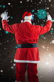 Composite image of rear view of santa claus listening to music. Rear view of Santa Claus listening to music against snowflake pattern Royalty Free Stock Photos