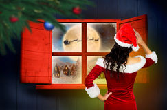 Composite image of rear view of sexy santa girl. Rear view of sexy santa girl against santa delivery presents to village Stock Images