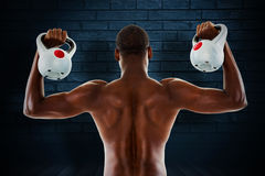 Composite image of rear view of shirtless fit man lifting kettle bells Stock Photography