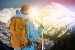 Composite image of rear view of skier with skis carrying backpack royalty free stock images
