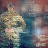 Composite image of rear view of soldier standing with his hands behind back Royalty Free Stock Photo