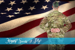 Composite image of rear view of soldier standing with his hands behind back royalty free stock photography