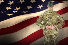 Composite image of rear view of soldier standing with his hands behind back stock photo