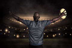Composite image of rear view of sportsman with arms raised holding rugby ball Royalty Free Stock Photo