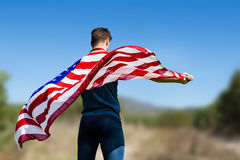 Composite image of rear view of sportsman holding an american flag Stock Image