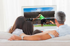 Composite image of rear view of sportsman throwing a shot. Rear view of sportsman throwing a shot against family watching television together on sofa stock image