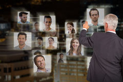 Composite image of rear view of stylish mature businessman pointing finger Royalty Free Stock Image