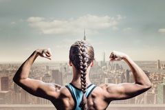 Composite image of rear view of woman with braided hair flexing muscles Royalty Free Stock Photo