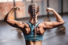 Composite image of rear view of woman with braided hair flexing muscles. Rear view of woman with braided hair flexing muscles against gym Royalty Free Stock Image