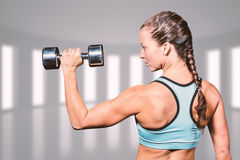 Composite image of rear view of woman lifting dumbbell Stock Images