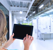 Composite image of rear view of woman using tablet pc Stock Images