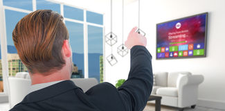 Composite image of rear view of young businessman in suit pointing. Rear view of young businessman in suit pointing against white sofas in modern living room Stock Photography