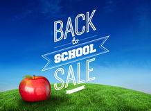 Composite image of red apple with back to school message. Red apple with back to school message against green hill under blue sky Royalty Free Stock Photos