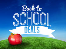 Composite image of red apple with back to school message. Red apple with back to school message against green hill under blue sky Royalty Free Stock Image