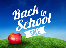 Composite image of red apple with back to school message. Red apple with back to school message against green hill under blue sky Stock Photo