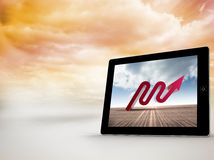 Composite image of red arrow on tablet screen Stock Image