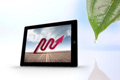 Composite image of red arrow on tablet screen Stock Photo