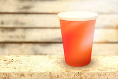 Composite image of red cup over white background. Red cup over white background against wood background Stock Image