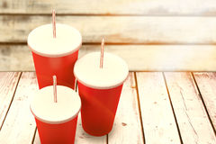 Composite image of red cups over white background. Red cups over white background against wood background Royalty Free Stock Photo