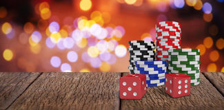 Composite image of red dice with stack of colorful casino tokens Royalty Free Stock Image
