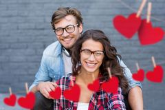 Composite image of red hanging heart and couple embracing each other. Composite image of red hanging heart and happy couple embracing each other against brick stock photos