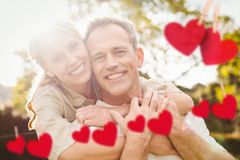 Composite image of red hanging heart and couple embracing each other stock illustration